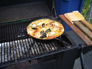 Grilling paella over a wood fire on a charcoal grill